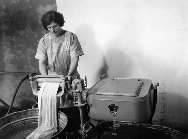 Woman Wringing Clothes with Early Washing Machine
