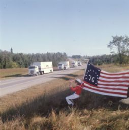 Young Girl with '76 Flag Watching Truck Caravan