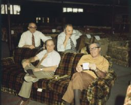 Four Men in Warehouse Full of Sofas