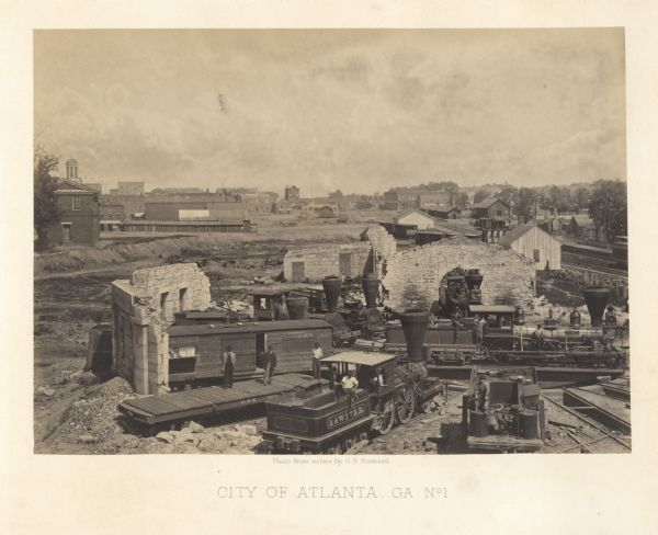 Elevated view of the ruins of the railroad roundhouse, with the city in the background. Men are posing on the train cars and engines. Plate 45