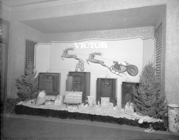 Christmas Victor radio show display in Orpheum theater lobby. There are four console radios and two Christmas trees. On the wall is a depiction of Santa in a sleigh pulled by reindeer.