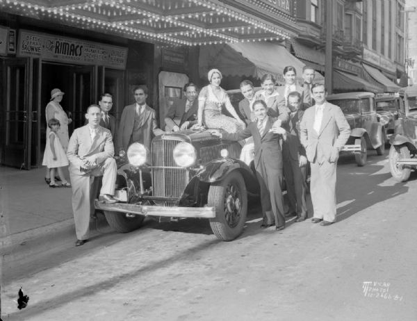 The Rimacs and their Havana Rumba Orchestra standing around a Nash automobile, the Kenosha twin ignition six, Model 990, in front of the Orpheum Theatre, at 216 State Street.