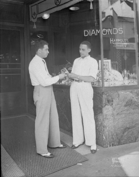 Harold Kohen, President of Harrold's Inc., jewelers, handing one of three watches he is contributing to Kiddy Camp auction, to Stephen Olsen, a brother of Ole Olsen in the Olsen and Johnson Comedy team. They are standing in front of Harrold's Jewelry store, 220 State Street.
