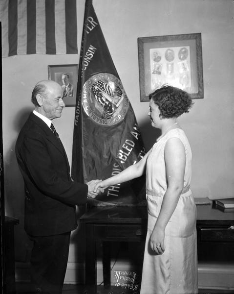 Mayor Albert Schmedeman holding the hand of Nina Westbury in front of the Morris O. Togstad Chapter 2 Disabled American Veterans of the World War flag.