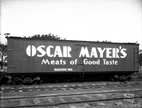 "Oscar Mayer refrigerated railroad freight car with ""Oscar Mayer's Meats of Good Taste"" advertisement on the side."
