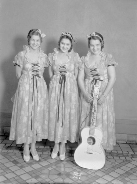 """Three Little Maids"", group portrait of three women, all standing, one holding a guitar, who performed with the WLS Barn Dance."