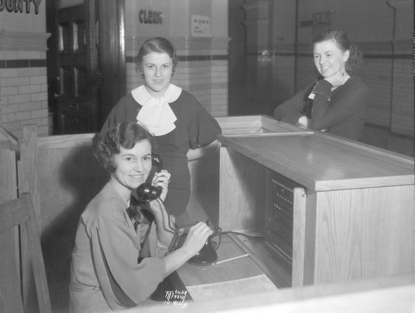 "Dane County Court House ""telephone girls"" at the new switchboard. Sitting at the switchboard is Madge Albright, and in the rear is Bernadine Plachy and Mary Davis."