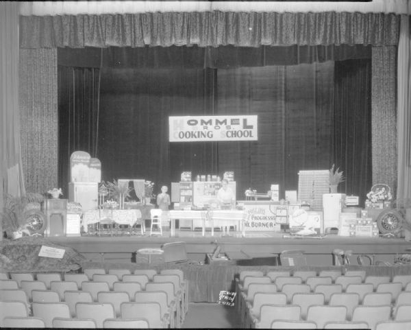 View from center aisle of Hommel's Cooking School set up on the Parkway Theater stage, 6-10 W. Mifflin Street. Displayed is a layout of the cooking demonstration as well as advertising for Johnston biscuits and crackers, Scott towels, Philco radios, Goodyear tires, and Karasnan rugs.