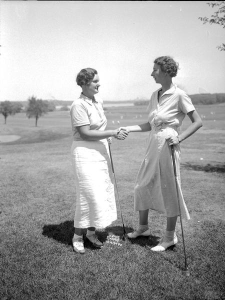Mary Callahan, Nakoma on the left, and Dorothy Page, Madison on the right, leaders in the qualifying round of the Wisconsin women's golf association tournament, shaking hands.
