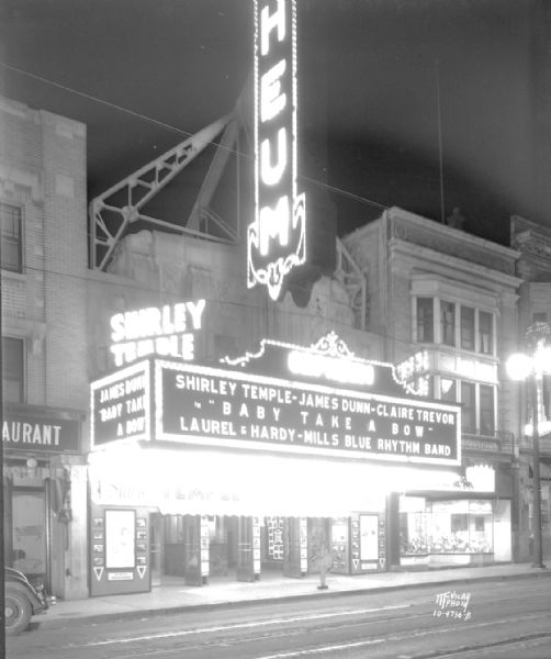 "View from street towards the Orpheum Theater marquee, which reads: ""Shirley Temple - James Dunn - Claire Trevor in Baby Takes a Bow, Laurel & Hardy - Mills Blue Rhythm Band."" The Thom McAn Shoe store is next door at 214 State Street."