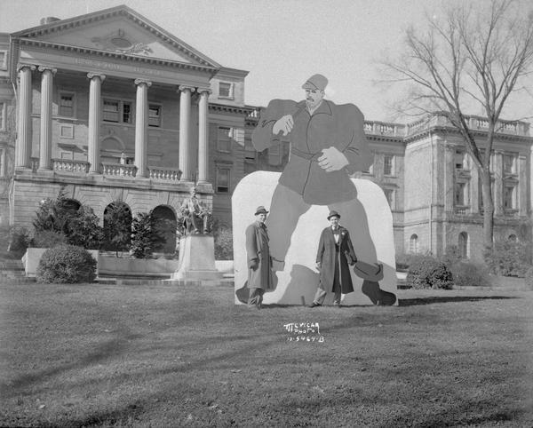 A Paul Bunyan figure used to celebrate University of Wisconsin Homecoming, was placed on the lawn in front of Bascom Hall. Two athletes are standing beside the figure, Edward Christianson, football player, and Gordon Fuller, basketball star. This effigy was later replaced by Paul Bunyan's Ax Trophy in 1948.
