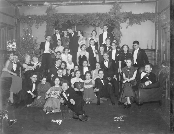 A group portrait of the Zeta Beta Tau Christmas formal, 216 Langdon Street, with two girls holding ZBT plaques with its crest.