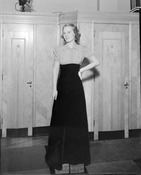 Female model wearing a long dress standing on blocks, part of fashion series from Kessenich's Ready to Wear, 201-203 State Street, showing store interior with wall of dressing room doors.