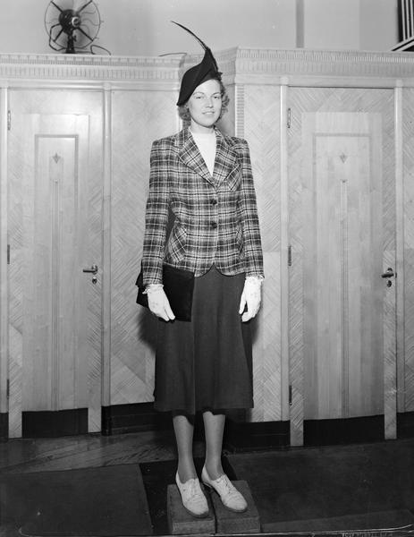 Model wearing hat, plaid jacket with plain skirt, wearing gloves, carrying purse, standing on blocks. Part of fashion series from Kessenich's Ready to Wear, 201-203 State Street, in front of dressing rooms.