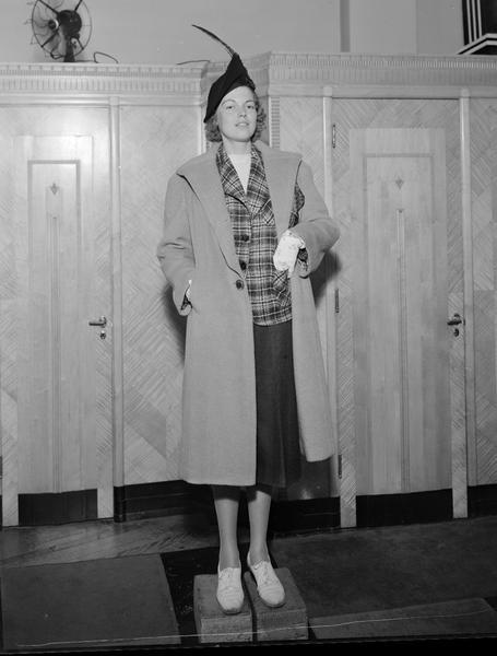 Model wearing hat and gloves, with coat over plaid jacket and plain skirt. The female model is standing on blocks. Part of fashion series from Kessenich's Ready to Wear, 201-203 State Street, in front of dressing rooms.
