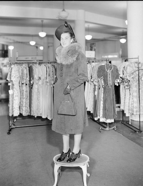 Model standing on step stool wearing hat and gloves, with fur collar coat, dress shoes, and carrying a purse. Part of the fashion series from Kessenich's Ready to Wear, 201-203 State Street, showing racks of dresses.