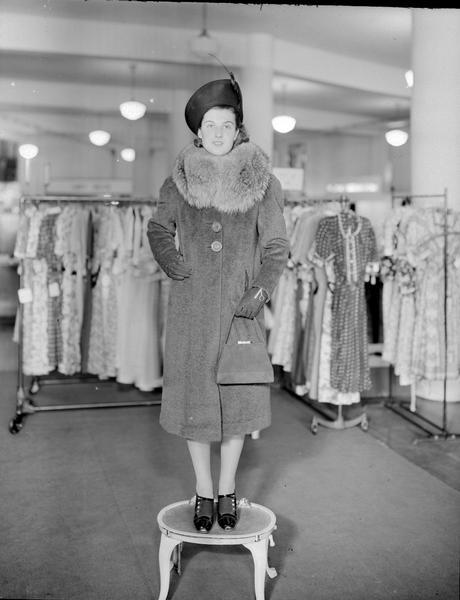 Model standing on step stool wearing hat and gloves, with fur collar coat, dress shoes, and carrying a purse. Part of a fashion series from Kessenich's Ready to Wear, 201-203 State Street, showing racks of dresses.