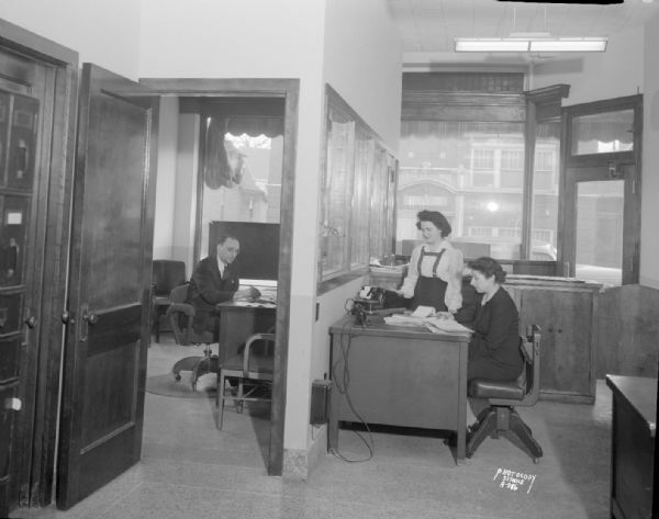 Madison News Agency, 446 West Gilman Street, office interior with room on left showing a man at a desk, and the room on the right showing two women at a desk with an adding machine.