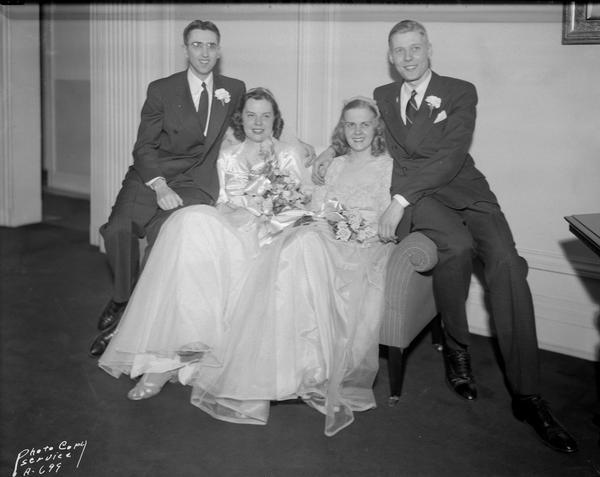 Bride and groom, Marjorie Bakken and William N. Schink, posing with the best man, Norbert Schmitz, and maid of honor, Vivian Milburn, posing at the Madison Club.
