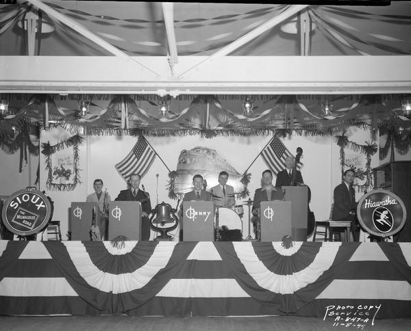 "Seven musicians in the Truax Field O. Henry Band on stage, decorated with banners, flags and logos of the Milwaukee Road ""Hiawatha"" and ""Sioux"" lines by the Milwaukee Road Employees Service Club, playing for the U.S.O. Carnival Week."