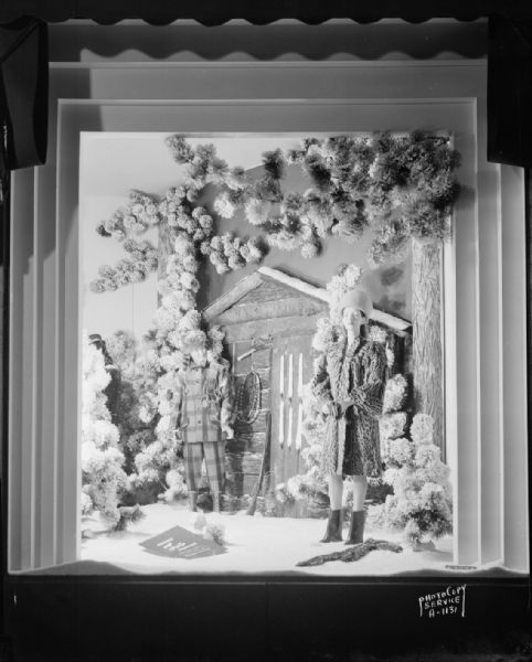 Manchester's, Inc., fur coat window display showing two mannequins, one wearing a fur coat and the other wearing a coonskin cap, standing in the snow in front of a log cabin, taken from Mifflin Street.