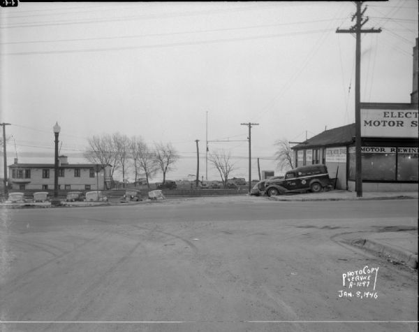 East Wilson Street scene at the center of South Hancock Street looking South down South Hancock Street across East Wilson Street, taken at site of Reynolds Bus accident. Businesses shown include the Four Lakes Boat Club at 1 South Hancock Street, and the Electric Motor Service at 323 East Wilson Street.
