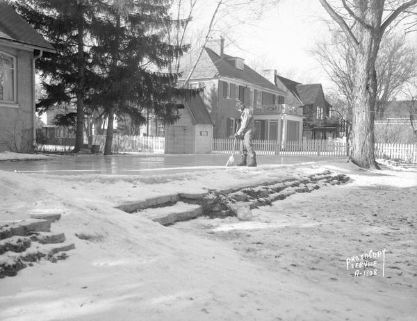 Arnold S. Zander sweeping ice skating rink at 175 Virginia Terrace. Photograph taken for AFSCME American Federation of State County and Municipal Employees of which Mr. Zanders was president. View includes snow slide, playhouse/warming house next to the rink, and three houses on Virginia Terrace.
