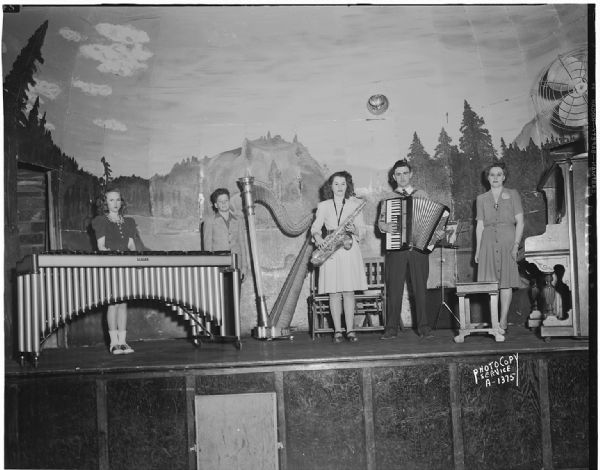 Three adult and two child musicians on stage with xylophone, harp, saxophone, accordion and piano at Smitty's Hall, for the grand opening program sponsored by the Milwaukee Cheese Company which opened a new cheese plant on April 1st.
