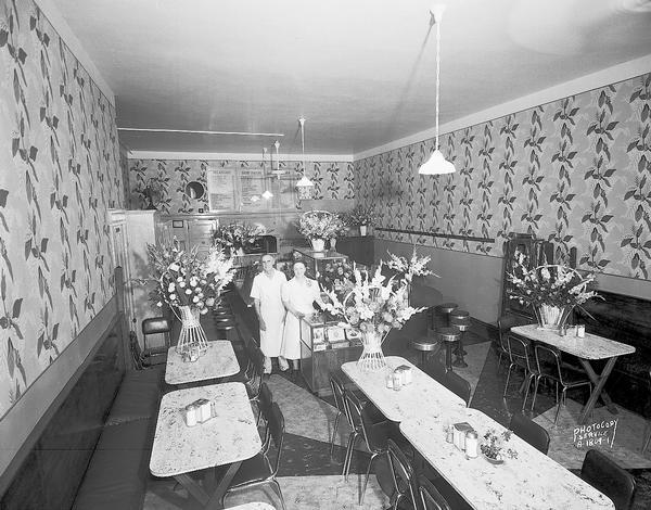 Slightly elevated view of Young's Cafe, 316 East Wilson Street. Joseph and Anna Young are standing in the cafe surrounded by bouquets on opening day.