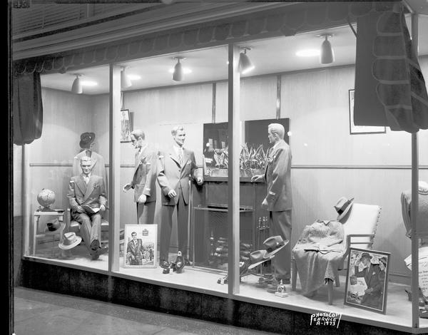 Angle view of four male mannequins in the window of The Hub clothing store, 22 West Mifflin Street.