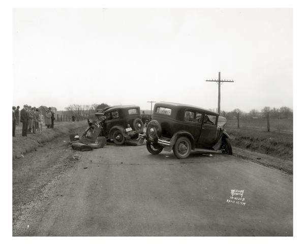 Onlookers surveying damage from a fatal two-car collision. The view is looking south on County Trunk Highway M, between Speedway Road and Middleton. In the accident Leo Maly was killed, and his wife, Edna, and son, Paul, and brother-in-law, Raymond Frisch, were injured. August Sternhagen, from Mazomanie, was also injured. This photograph was taken by news photographer Angus McVicar. His collection in the Archives, as well as those of numerous other Wisconsin newspaper photographers, testify to both the frequency and destructiveness of automobile accidents even during the automobile's early days.