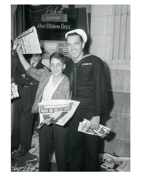 Seaman 1st class Tom Teeley with newsboy, Bernard Ehrmann, holding a copy of the Wisconsin State Journal with headline declaring peace in the Pacific.  Celebrating V-J Day, August 15, 1945, the day on which the Allies announced the surrender of Japanese forces during World War II.