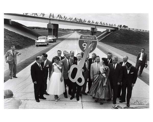 Dedication of Wisconsin's first expressway, a seven-mile stretch of Interstate Highway I-94 in Waukesha County, Wisconsin. Presiding at the ribbon-cutting ceremony are several government officials and Miss Concrete and Miss Black Top.  Holding the large pair of scissors is Governor Vernon Thomson and to his right is Secretary of State Robert Zimmerman.  Warren Knowles, who would later become governor, is also in the crowd.