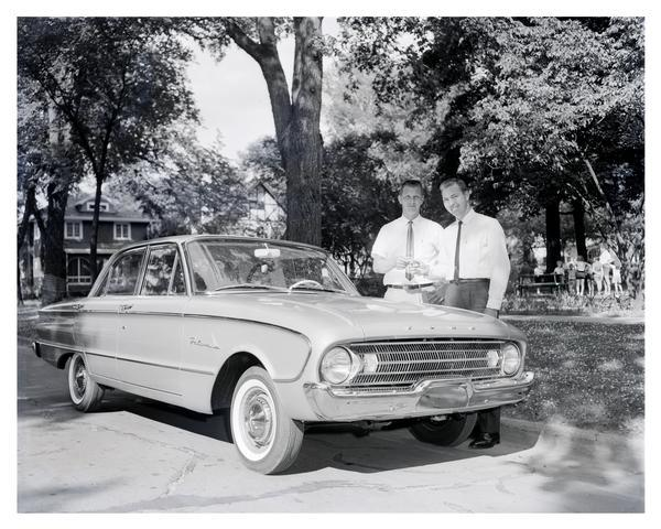 Bart Starr of the Green Bay Packers receives a new 1961 Ford Falcon from a Green Bay Ford dealer. The compact Falcon was introduced by Ford in 1959 to appeal to drivers seeking better mileage. It was available in several styles in addition to the four-door sedan seen here, including convertibles and station wagons, and it was immediately popular with car buyers. The Falcon also served as the framework for the Ford Mustang. Production of the Falcon in the United States ended in 1970.