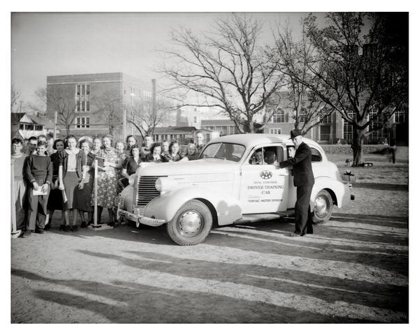 AAA driver's training instructor with group of students, posing with dual control driver's education car, in front of Madison East High School.