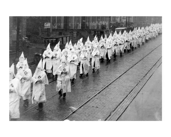 "Ku Klux Klan (KKK) wearing conic masks and white robes parading down King Street to Schroeder Funeral Home for the funeral of Police officer Herbert Dreger.  Dreger was shot to death in ""Death's Corner"" (South Murray Street) on December 2, 1924."