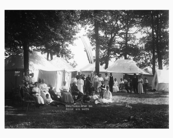 Families gathered in front of large tents at a Chautauqua meeting.
