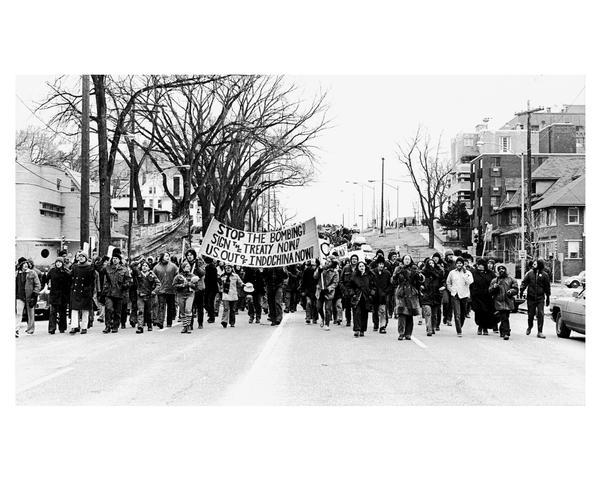 "A crowd of anti-Vietnam war demonstrators march down Wisconsin Avenue with signs and banners. One banner reads ""Stop the Bombing. Sign the Treaty Now! U.S. Out of Indo-China Now!""."