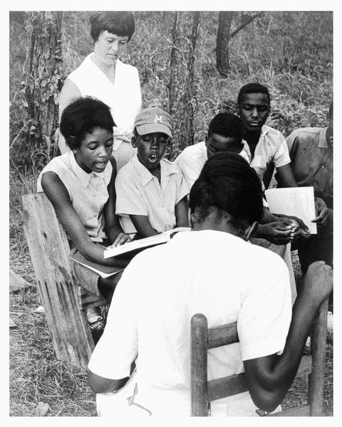 A group of African American students participating in a Freedom School class outdoors during Freedom Summer. The class, which was held on Tougaloo College campus, was led by Joanne Gavin, who is standing behind the students. Seated on the far left is Hymethia Washington, who is holding a book. Charles, who is wearing a baseball cap, is sitting next to Hymethia.