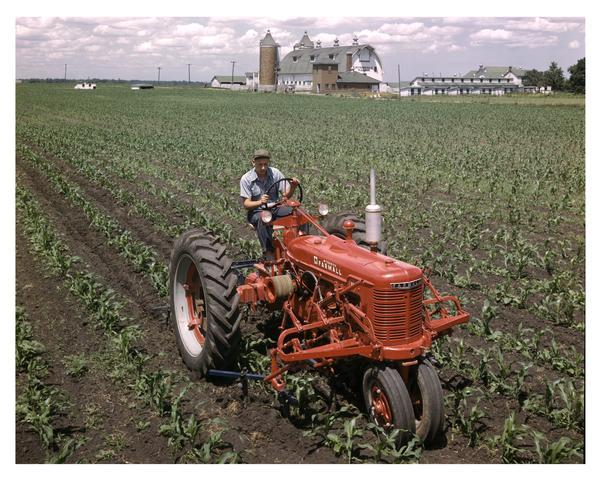Slightly elevated view of a man using a Farmall H tractor near International Harvester's experimental farm.