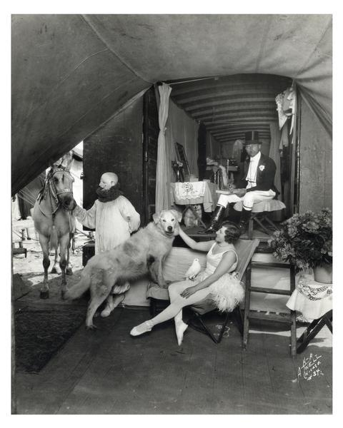 Fred and Ella Bradna, equestrian director and performer for Ringling Brothers, Barnum & Bailey. There are several other performers and a dog, relaxing in their circus wagon.