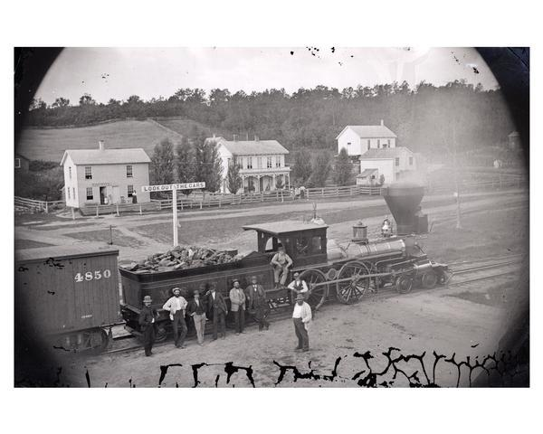 Elevated view of several men, some of whom may be railroad workers, posing in front of a Minnesota and St. Paul wood-burning engine at a train crossing. The town post office and other structures can be seen behind the train. Station master, Samuel Barber, is fifth from left.