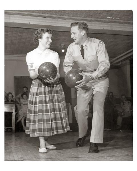 A USO volunteer challenges an enthusiastic soldier to a friendly bowling match.