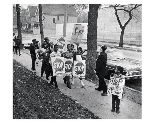 "Father James Groppi (1930-) and school desegregation demonstrators marching in Milwaukee holding signs that read ""Stop School  Segregation""."