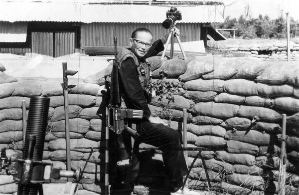 Dickey Chapelle on the Don Phuc command post, in front of a stack of sandbags, on the Vietnam-Cambodia frontier. Chapelle resided at this post for 34 days, photographing combat and participants.