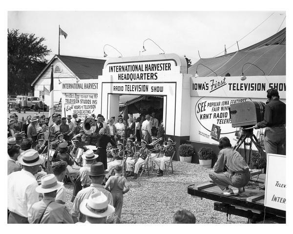 International Harvester tent and exhibition at the Iowa State Fair. This image includes workers filming Iowa's first television show and a high school brass band entertaining fair-goers.
