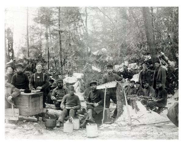 Loggers at dinner in the woods north of Glen Flora. The man in the center is filing his saw.