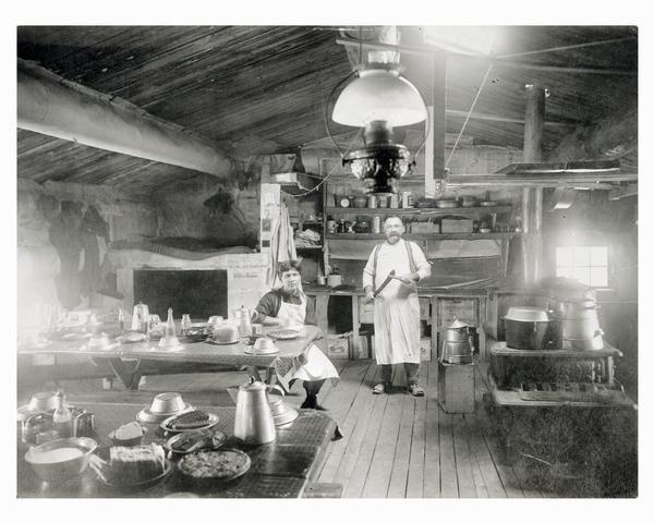 Two men preparing a meal in a lumber camp shanty or bunkhouse.