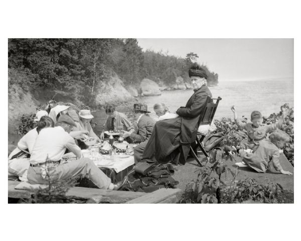 Picnic on the shores of Basswood Island, Apostle Islands. Those picnicking include Harriet Webb, C.A. Hull, H.W. Rodgers, Mrs. J. Austin, Elizabeth Baker, Mrs. J.L. Abernathy, and two Austin children.
