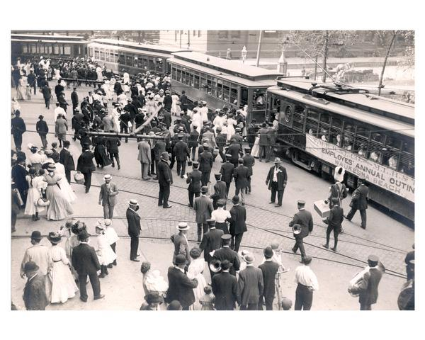 In a festive mood, Milwaukee Electric Railway and Light Company employees disembark from flag-decked trolley cars to enjoy a company-sponsored outing. The company hired trolley cars to Waukesha Beach. Recreation included picnicking, ball games, and potato races.